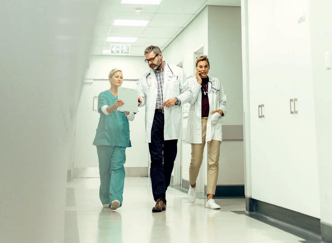 Ärzte mit Personal läuft durch Krankenhausgang
