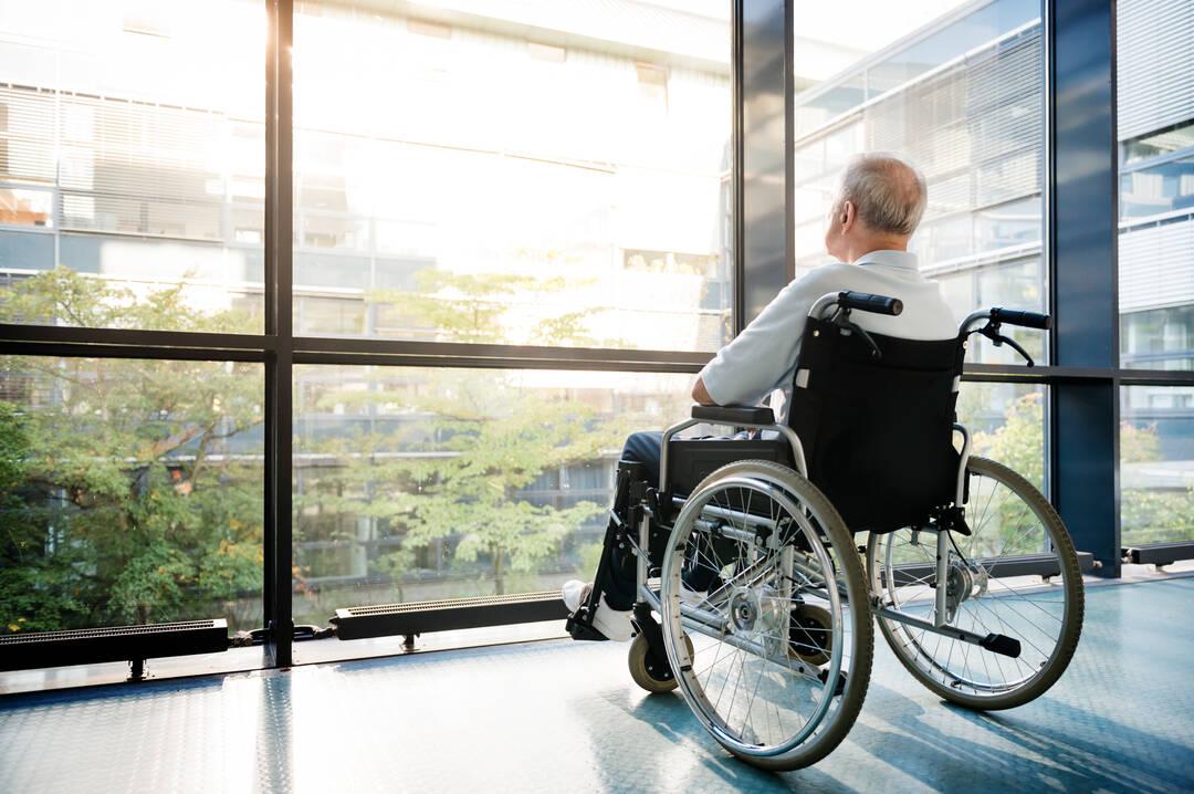 Mann sitzt in Rollstuhl vor Fenster einer Senioreneinrichtung